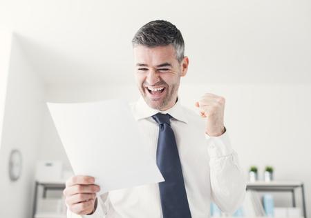 Fröhlich Geschäftsmann im Büro eine gute Nachricht empfängt, ist er ein Vertragsdokument hält und die Erhöhung seiner Faust