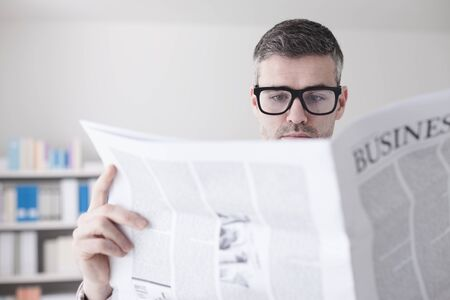 financial newspaper: Confident businessman with glasses reading a financial newspaper in his office