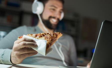 L'homme à la maison de manger une tranche de pizza et le réseautage social avec un ordinateur portable tard dans la nuit