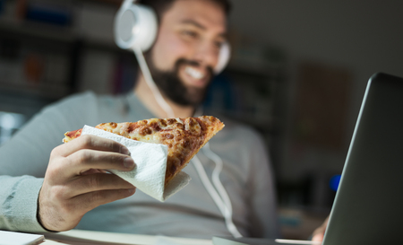 pizza: Man at home eating a slice of pizza and social networking with a laptop late at night