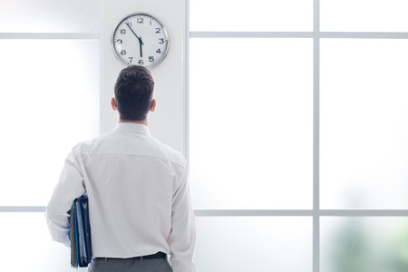 office slave: Businessman in the office staring at the clock, back view, time slave and stress concept
