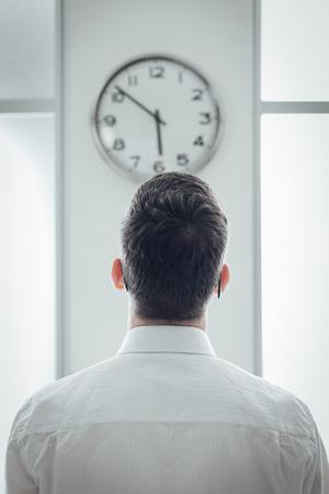 detras de: Hombre de negocios en la oficina mirando el reloj, vista posterior, esclavo tiempo y concepto de la tensión