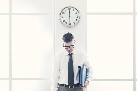 standing businessman: Frustrated businessman in the office standing under a clock, punctuality and time slave concept Stock Photo