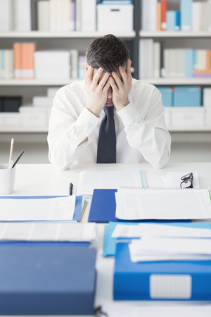 hands on head: Stressed exhausted man working at office desk with head in hands, he is overloaded with paperwork, stressful job concept