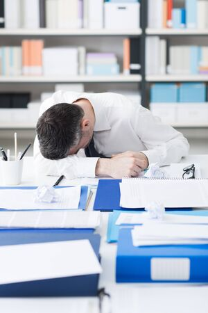 over burdened: Exhausted businessman overloaded with paperwork, he is collapsed and sleeping on his desk, stress and overwork concept