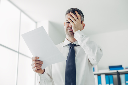 and white collar workers: Desperate office worker receiving a dismissal letter from his boss, loss of job and unemployment stress concept Stock Photo
