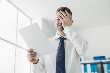 Verzweifelte Büroangestellte eine Entlassung Brief von seinem Chef, Verlust des Arbeitsplatzes und die Arbeitslosigkeit Stress-Konzept Empfang Standard-Bild