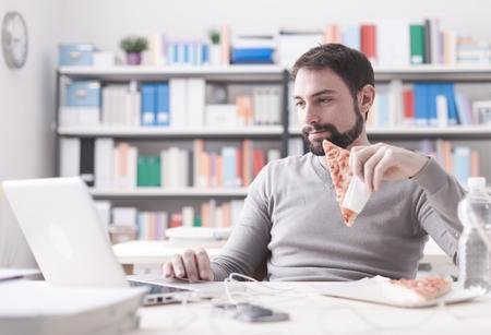 Lächelnder Mann, eine Mittagspause im Büro, er isst ein Stück Pizza und Social-Networking mit einem Laptop