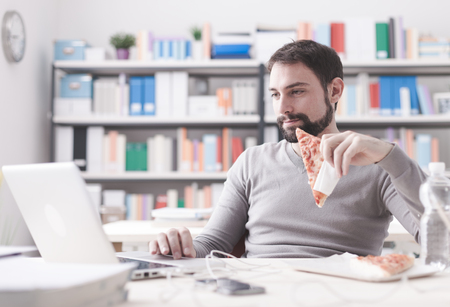 Smiling man having a lunch break at office, he is eating a slice of pizza and social networking with a laptop