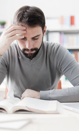 self improvement: Adult focused man sitting at desk and studying at the library, learning and self improvement concept
