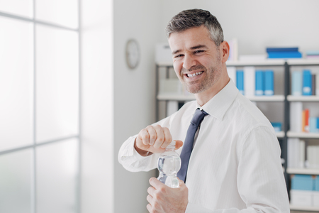 drink water: Cheerful office worker holding a water bottle and smiling at camera, healthy lifestyle concept