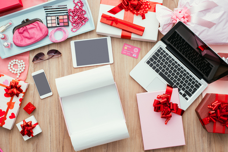 unwrapping: Open empty gift box on a desktop with a laptop, a credit card and beauty accessories, online shopping and fashion concept