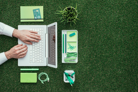 Zakenman met behulp van een laptop op het gras buiten; green business en technologie concept, bovenaanzicht Stockfoto