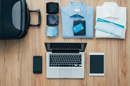Planen Sie eine Geschäftsreise: Beutel, formelle Kleidung, Kreditkarten und Flugtickets auf einem Schreibtisch mit Laptop, Smartphone und Tablet, Reisen und Technologie-Konzept