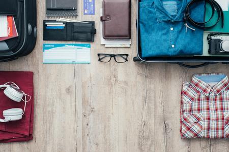 Zich klaar voor een reis en het verpakken van een koffer voor vertrek; accessoires, kleding en persoonlijke spullen op een desktop, reizen en vakanties begrip