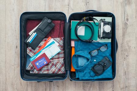 衣料品、アクセサリー、クレジット カード、チケット、パスポート、旅行や休暇の概念と旅行者のバッグを開く