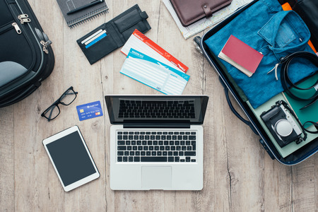 Traveler packing and getting ready for a trip, desktop with baggage, tickets, credit card, laptop and digital tablet, flat lay