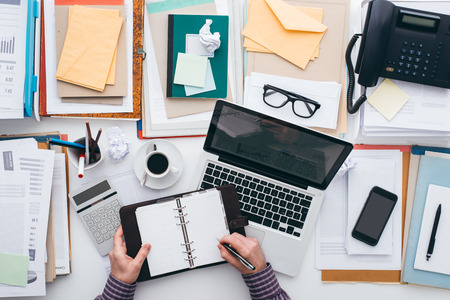 file clerks: Businessman scheduling appointments on his organizer and full desktop with paperwork and a laptop, flat lay