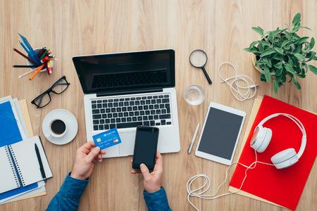 El hombre de compras en línea en casa utilizando un ordenador portátil y una tarjeta de crédito, que está haciendo un pago por móvil utilizando su teléfono inteligente, vista desde arriba Foto de archivo