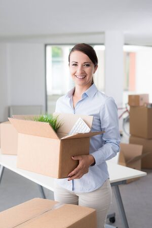 mujeres morenas: Smiling business woman carrying cardboard boxes into her new office, she is smiling at camera