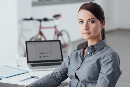 Beautiful businesswoman sitting at office desk and posing, she is smiling at camera photo