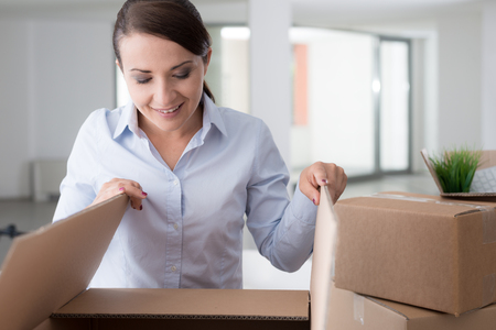 home business: Happy curious woman unpacking and moving into her new office, she is opening a cardboard box and looking into it