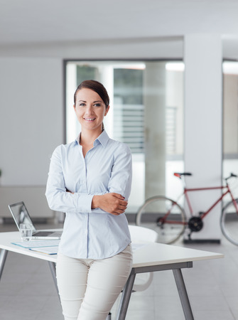 Beautiful woman leaning on office desk and smiling at camera photo