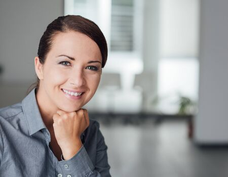 Beautiful businesswoman posing, she is smiling at camera with hand on chin photo