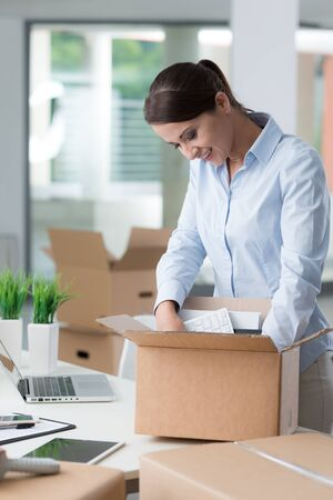 brunette woman: Smiling business woman unpacking a cardboard box in her new office on her desk, new job and relocation concept