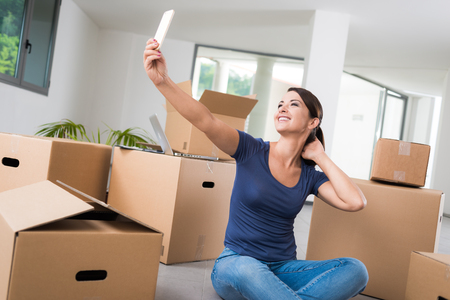 Confident woman taking a selfie with her mobile in her new house, she is sitting on the floor with lots of carton boxes photo