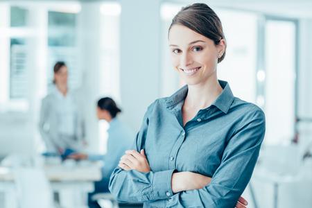 Lächelnde weibliche Büroangestellte posiert mit verschränkten Armen und Blick in die Kamera, Büro-Interieur auf Hintergrund