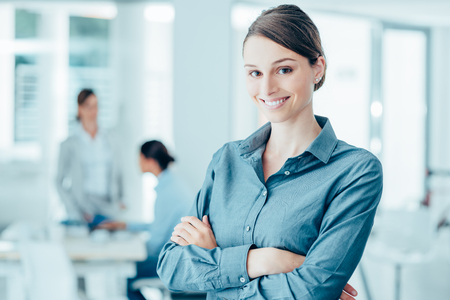 Smiling female office worker posing with arms crossed and looking at camera, office interior on background