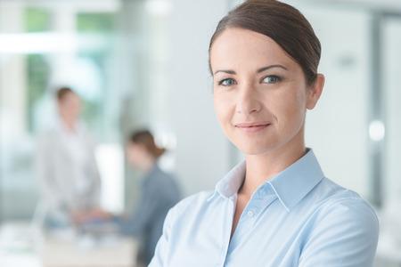 El éxito de negocios que presenta en su oficina y sonriendo a la cámara, los trabajadores de oficina en el fondo, el enfoque selectivo