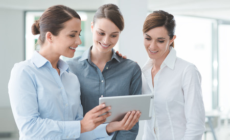 they are watching: Professional smiling business women standing in the office and using a touch screen tablet, they are enjoying and watching the screen
