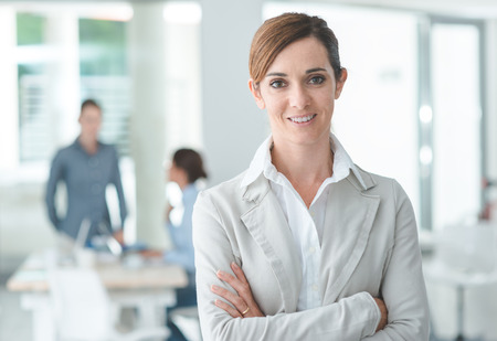 woman white shirt: Confident woman entrepreneur posing in her office and smiling at camera, success and women empowerment concept Stock Photo