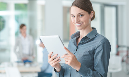 executive women: Confident smiling business woman standing in the office and using a digital tablet, business people working on background