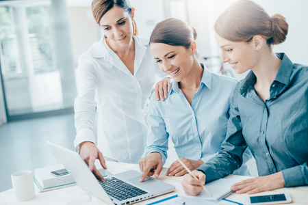 only women: Smiling business women team working at office desk and discussing a project on a laptop Stock Photo