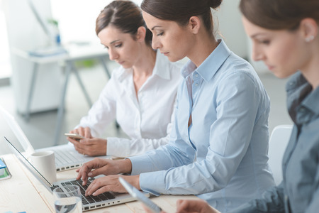 Efficient business women working together at office desk using laptops and mobile devices, women entrepreneurs concept Stock Photo