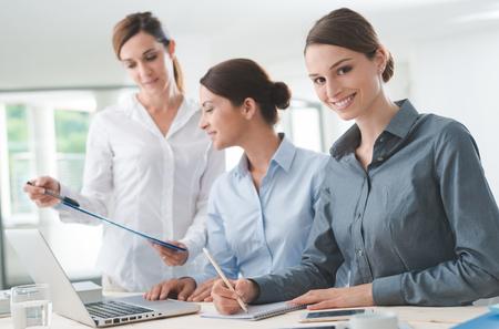 personas dialogando: Las mujeres de negocios equipo de trabajo en el escritorio de oficina y que señala en un informe, uno está sonriendo a la cámara