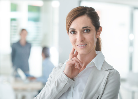 confident business woman: Confident woman entrepreneur posing in her office and smiling at camera, success and women empowerment concept Stock Photo