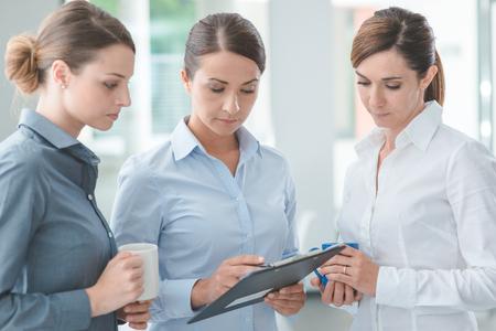 Professionnel équipe de femmes d'affaires pointant sur un presse-papiers et de discuter au cours d'une pause-café