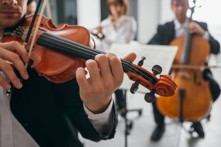 unrecognizable people: Violinist performing on stage with classical music symphony orchestra, hands close up, selective focus, unrecognizable people Stock Photo