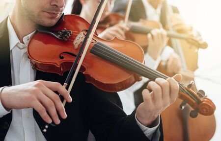 violinista: Classical music symphony orchestra string section performing, male violinist playing on foreground, music and teamwork concept
