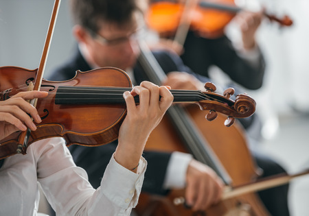 orquesta clasica: Female violinist performing and classical orchestra on background, selective focus, music and arts concept