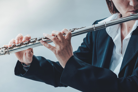 the transverse: Professional elegant female flutist performing in a white room, hands close up