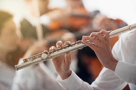 클래식 음악 심포니 오케스트라와 함께 수행하는 전문 여성 플루트 플레이어, 인식 할 수없는 사람