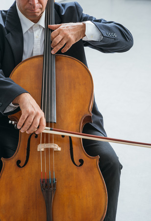 cellist: Professional male cellist playing his cello, classical music solo performance
