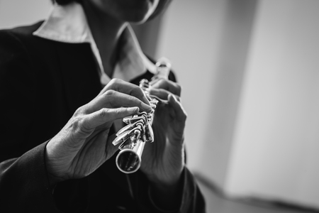 soloist: Professional elegant female flutist performing in a white room, hands close up