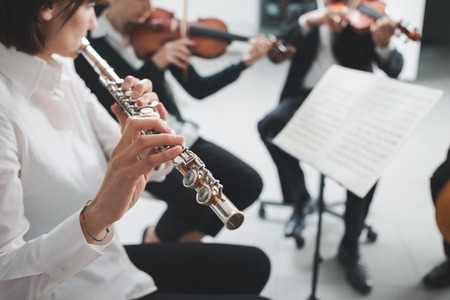 professional flute: Professional female flustist playing her instrument on stage with classical music symphony orchestra