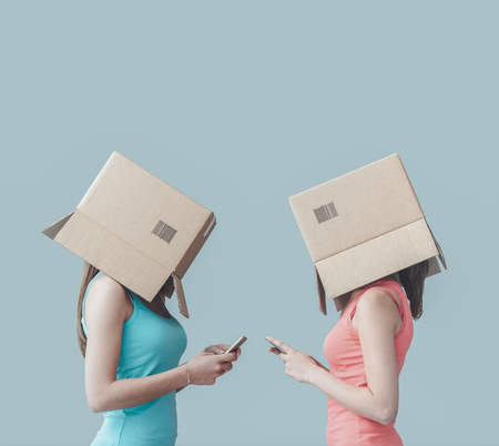 inexpressive: Adolescent girls with boxes on their heads texting with their smart phones, social networks and isolation concept